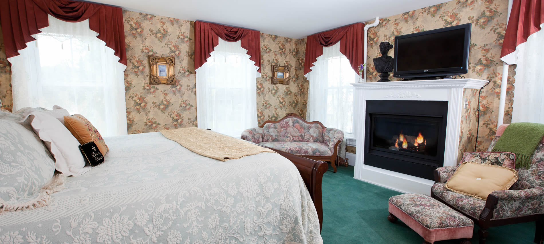 Princess Alice guest room, floral wallpaper, teal green carpet, fireplace, TV, upholstered furniture and several windows