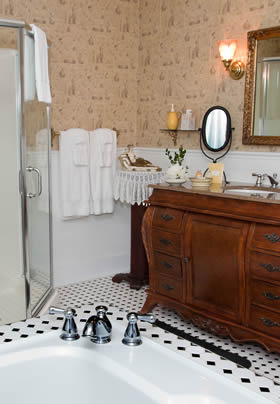 Princess Alice guest bath with peach papered walls, black and white tiled floor, tub, corner shower, and antique vanity