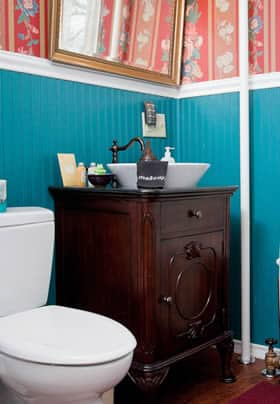 Princess Beatrice guest bath with turquoise beadboard, pink and blue papered walls, and antique vanity with vessel sink