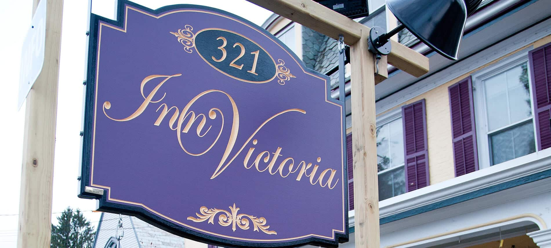 Exterior post and sign in front of the inn with 321 Inn Victoria engraved on a purple background