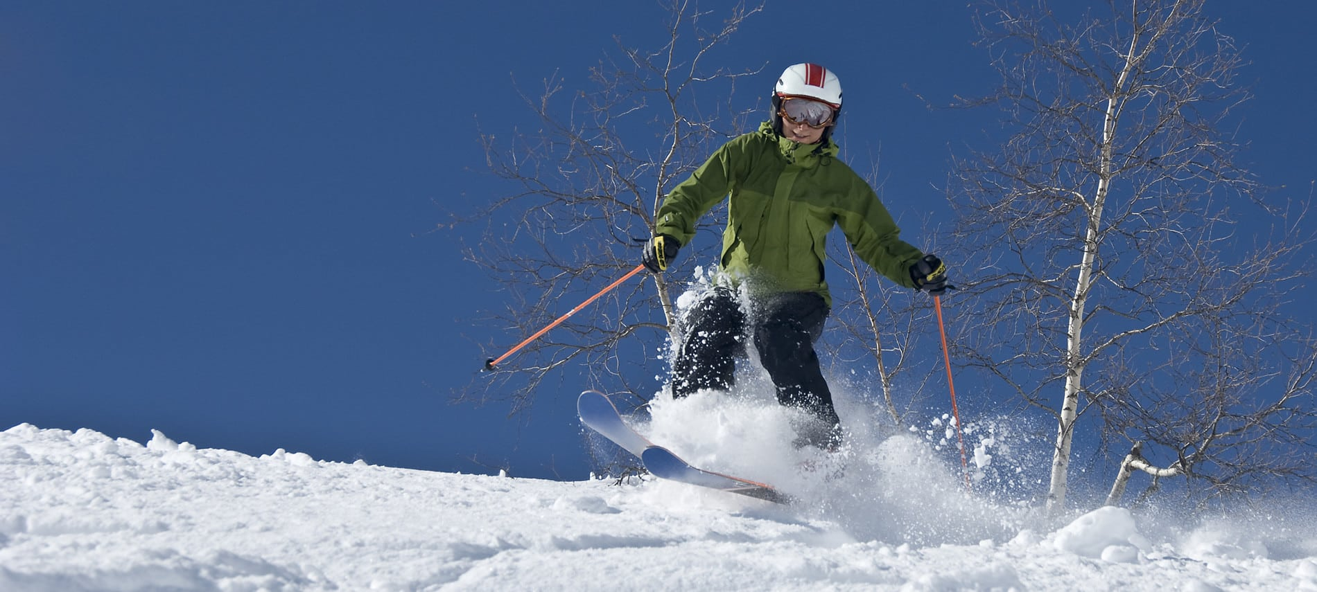 Person snow skiing down hill amidst crisp blue skies