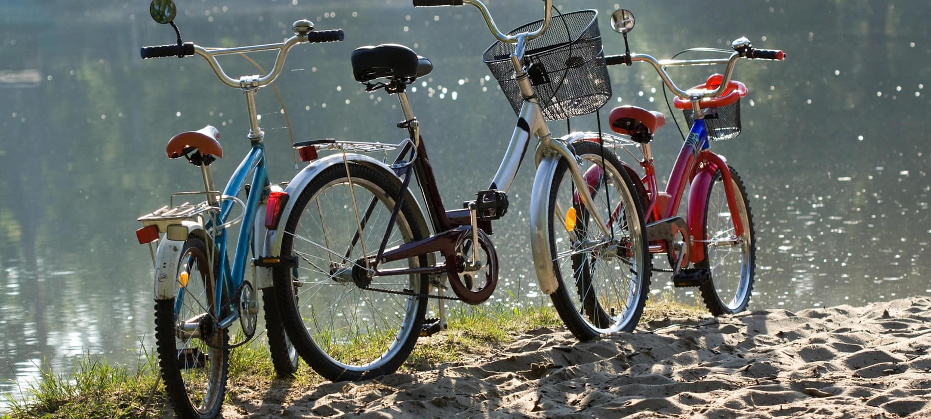 Three colorful bicycles parked on the sand next to a body of water