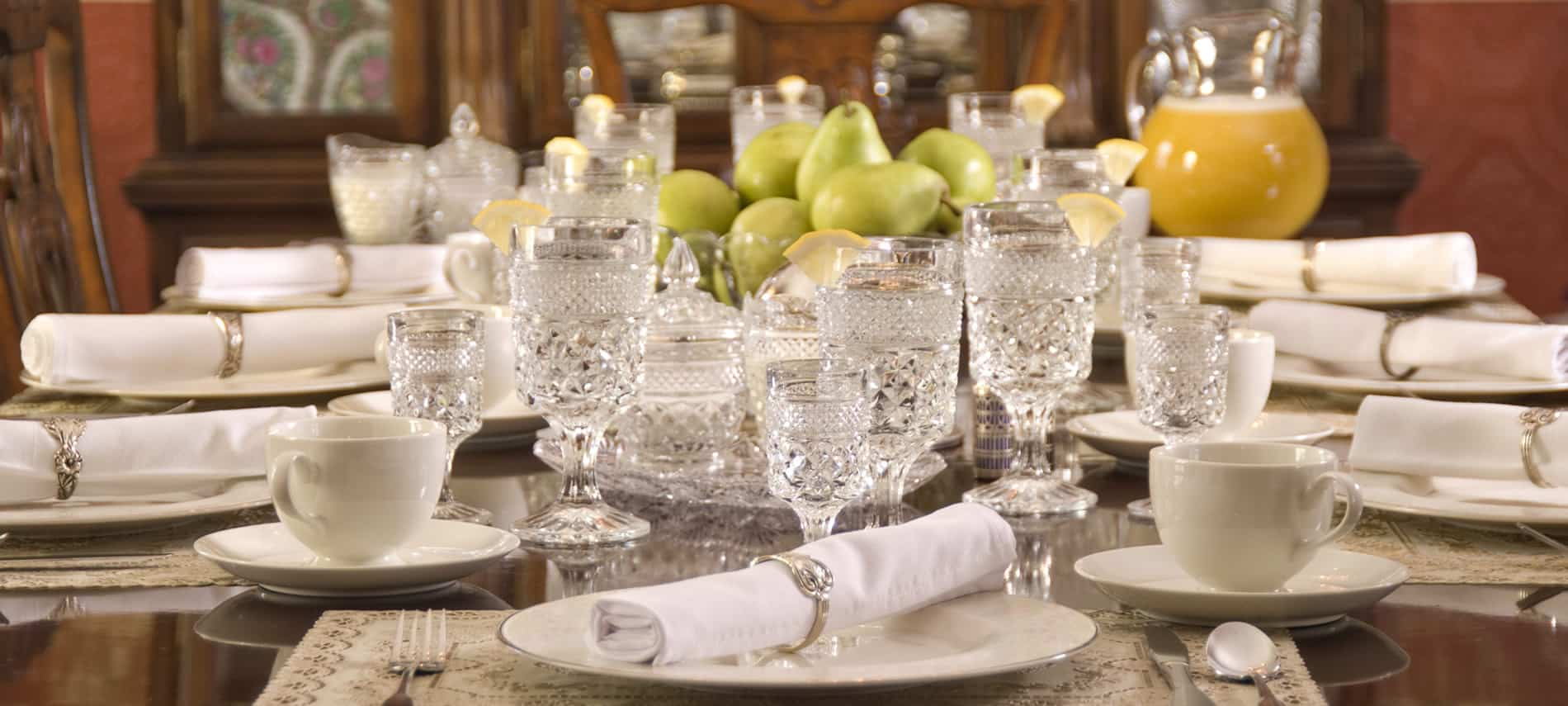 Close-up view of dining table set for a meal with ivory china, white napkins, and crystal glassware