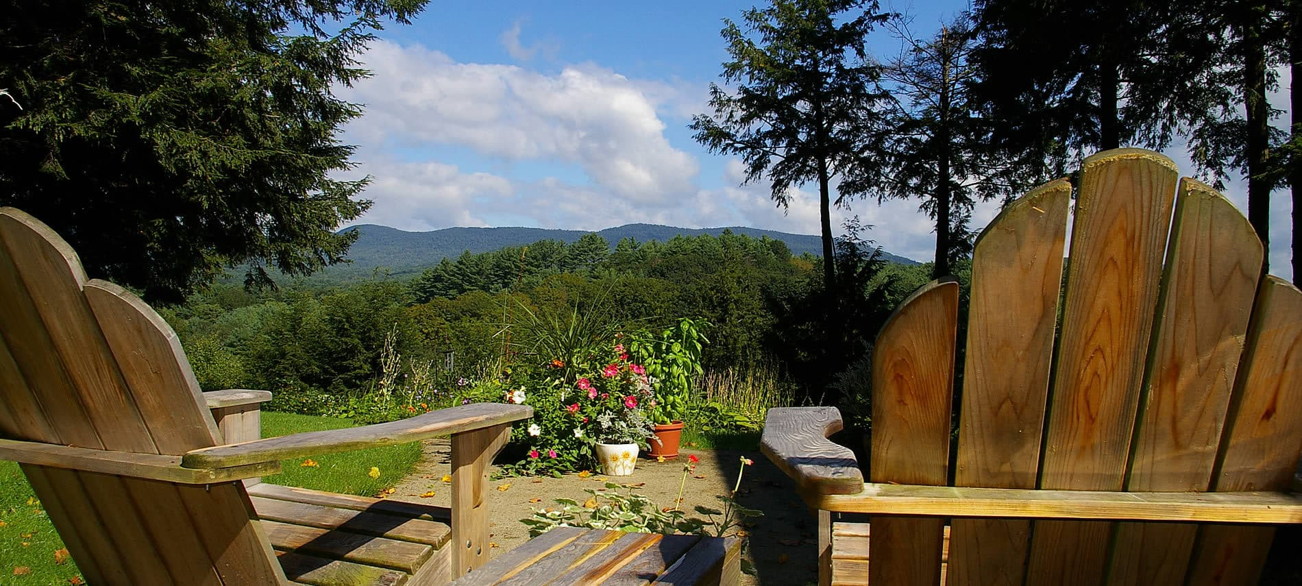 Two wooden Adirondack chairs looking toward the distant hills and trees amidst blue skies