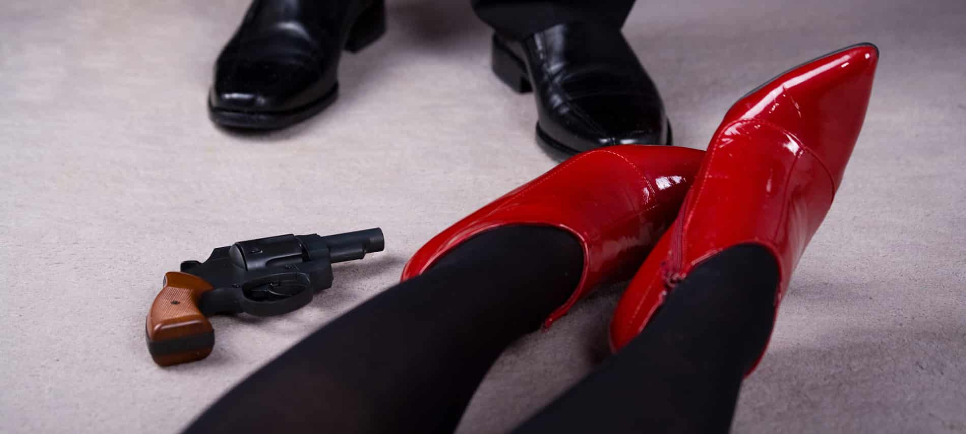 "Image of two pairs of feet. One pair of feet suggests a woman laying down, with a revolver at her feet and the other a ""detective esque"" pair of shoes investigating."