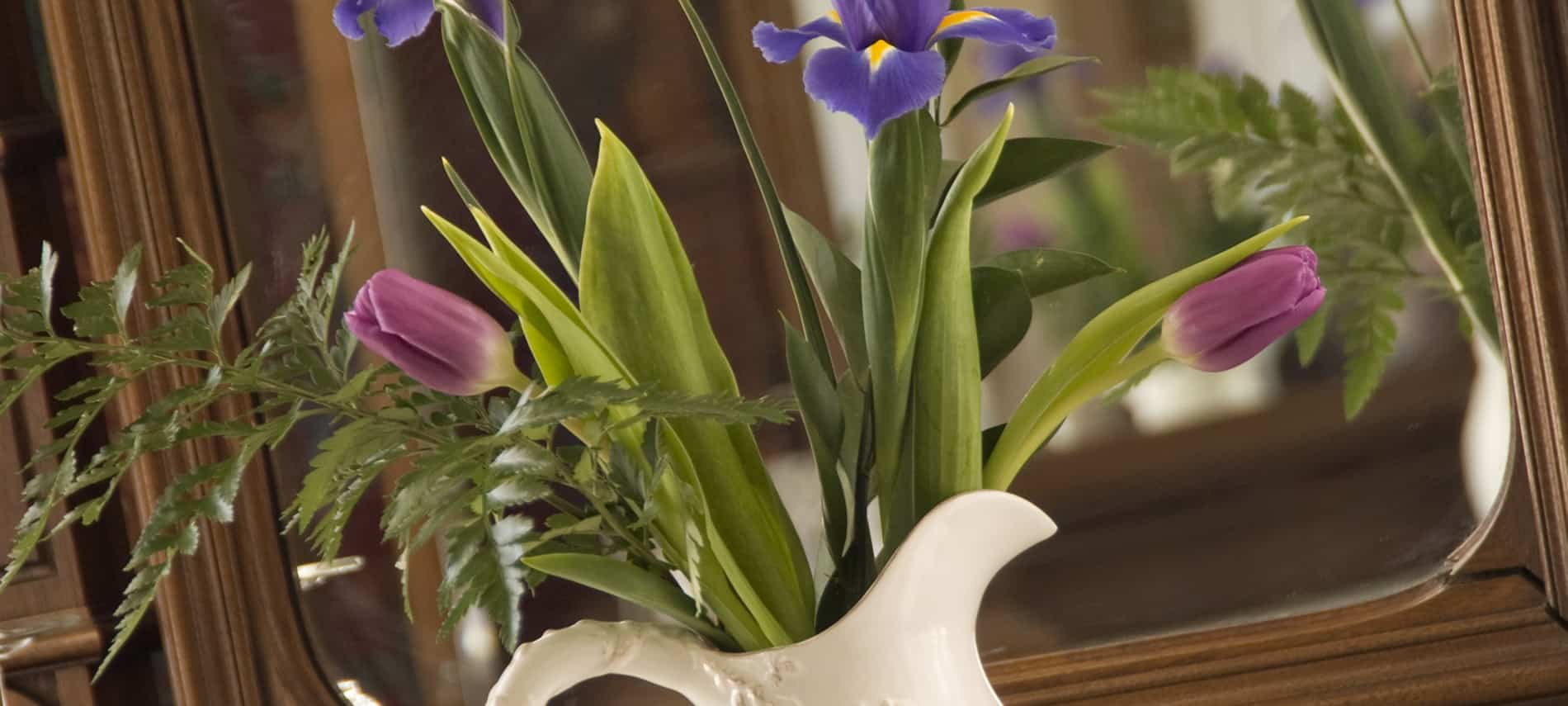 White vase filled with mauve and purple and yellow flowers with green stems and leaves