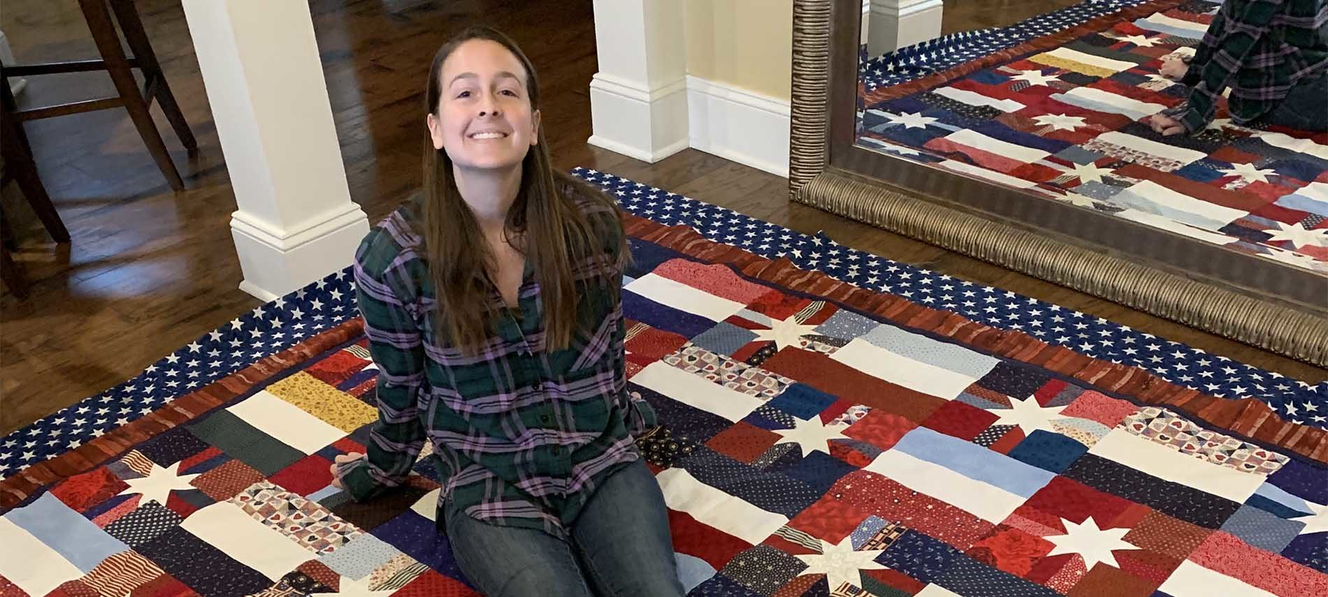 Young woman sitting upon a quilt stretched across a spanse of floor with mirror to show a different angle. Quilt pattern is white 8 point stars on different fields.