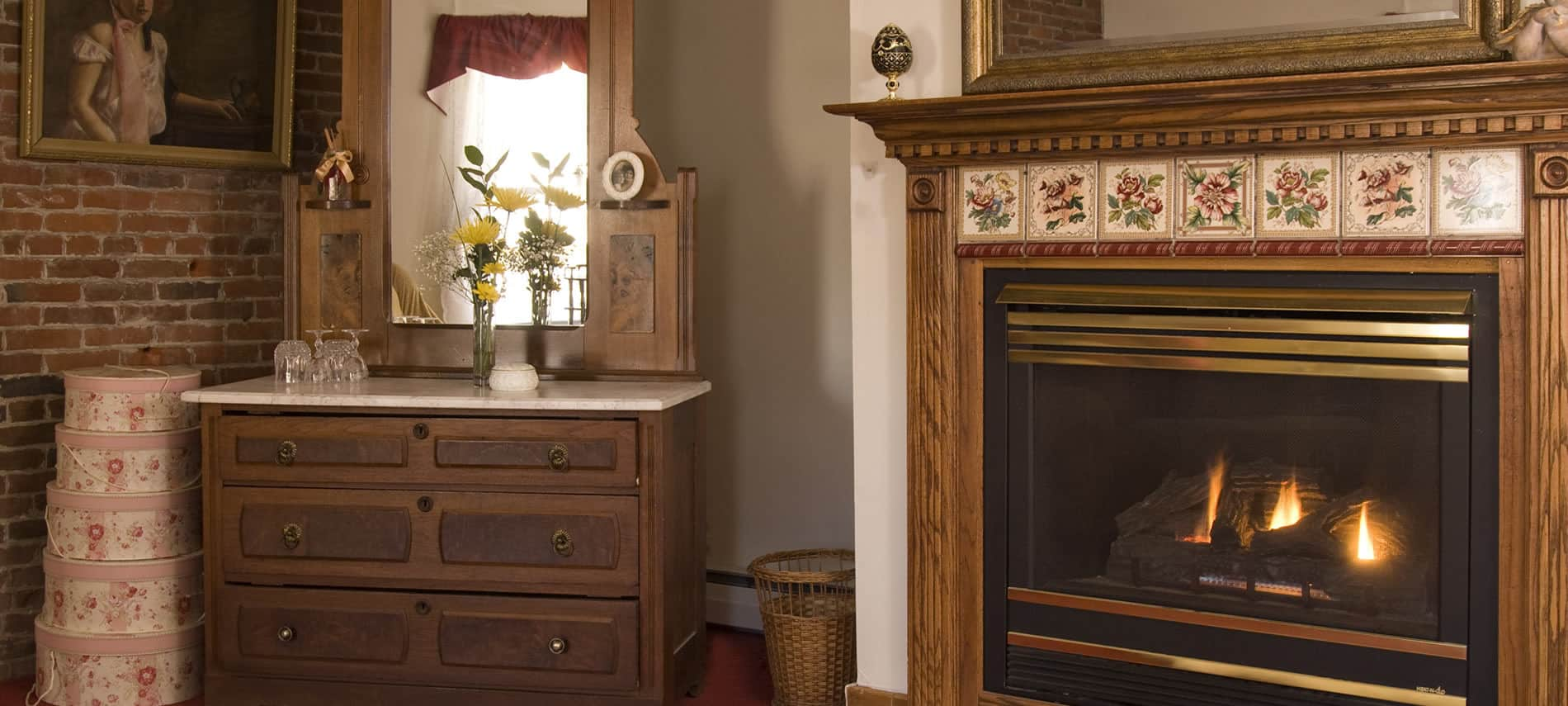 Fireplace with wood wrap around mantel and decorative tile inserts, corner chest with mirror, and brick wall with framed portrait