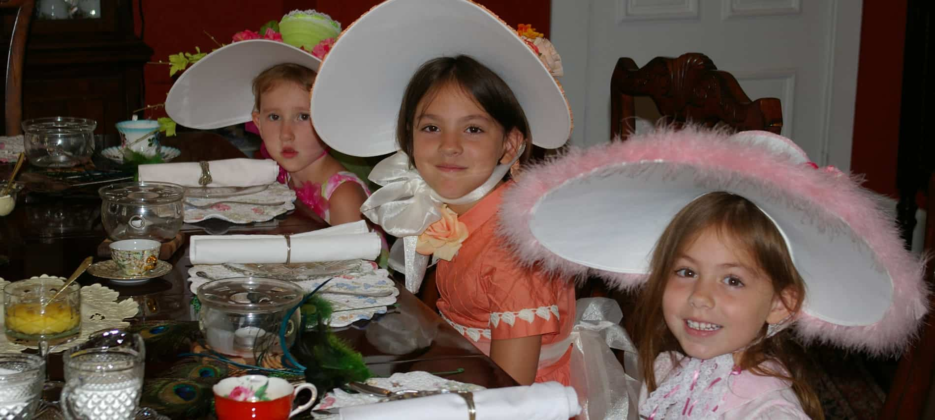 Three young girls wearing fancy dresses and large hats sitting at an elegant table set for tea