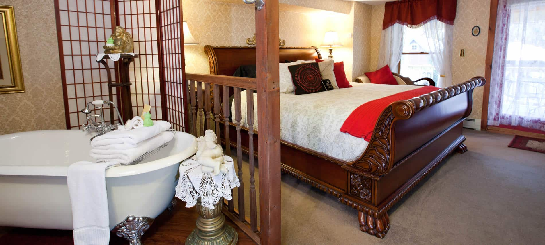Princess Helena guest room, ivory paper walls, carved wood bed with ivory bedding, and claw foot tub behind screen dividers