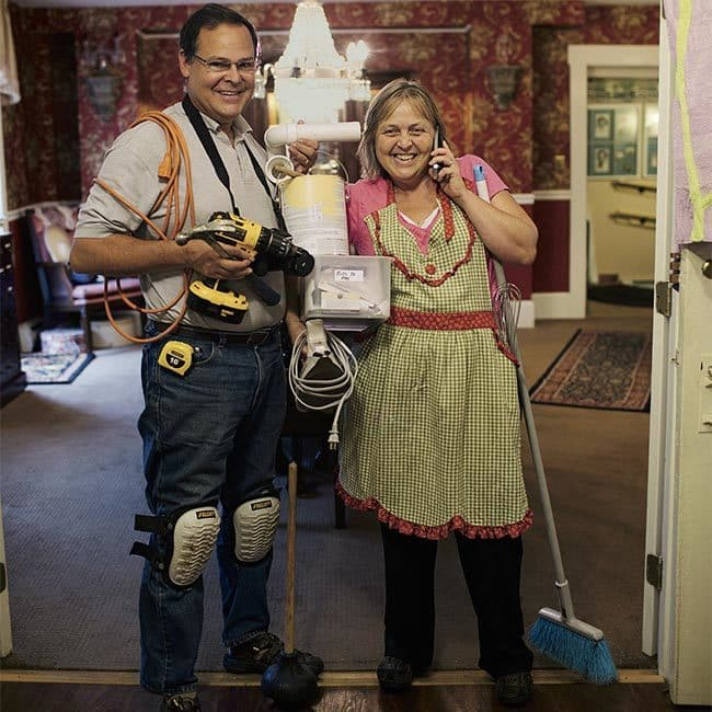 Innkeepers wearing the tools of their trade. Woman in apron with wire wisk, and phone to ear, man with power tools, cord, hammer, and paint bucket both holding a bin notated