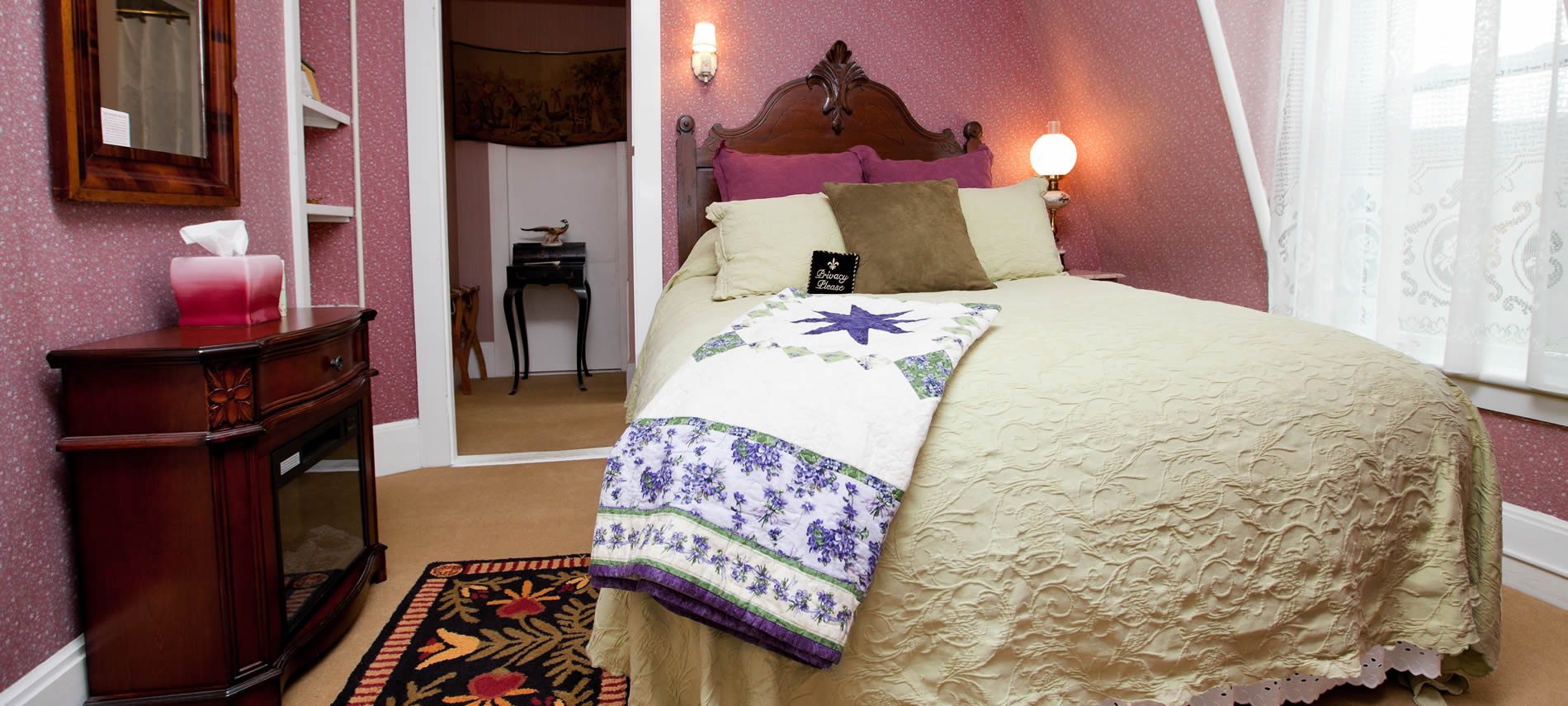 Prince Leopold guest room with pink papered walls and carved bed with ivory bedding, and window