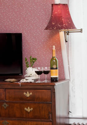Prince Leopold guest room with pink papered walls, dresser topped with wine bottle and glasses and white window sheers