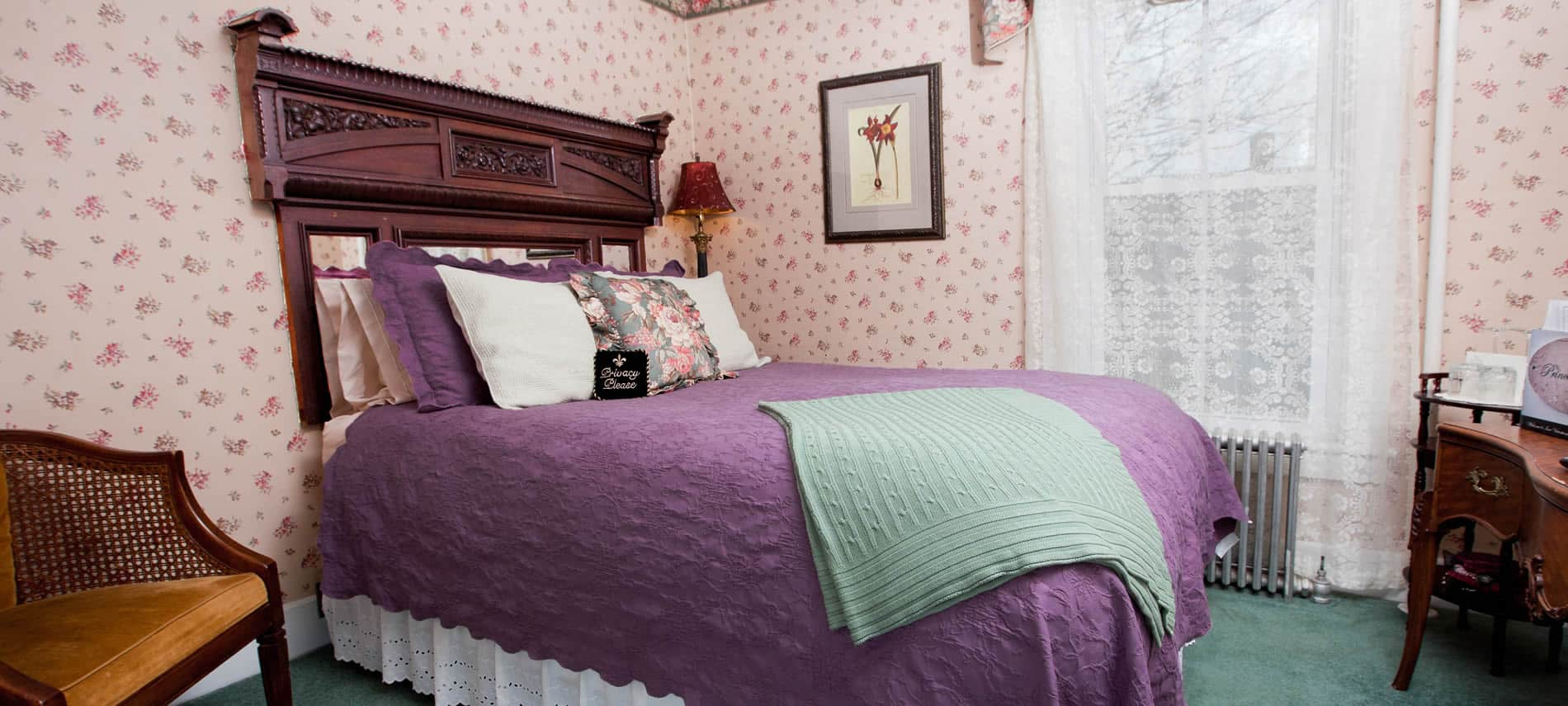 Princess Louise guest room, tiny floral papered walls, carved headboard, and purple bedding