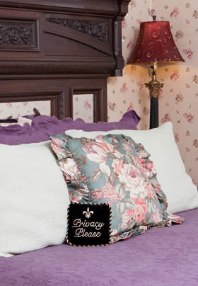 Princess Louise guest room bed with purple bedding, white and floral pillows, and carved wood headboard
