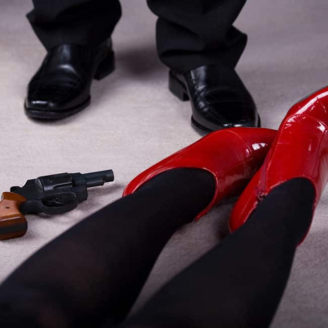 Murder Mystery Suspense Image: An image of a woman's legs and feet, lying next to a revolver and