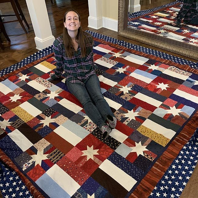 Young woman sitting upon a quilt stretched across a spanse of floor with mirror to show a different angle. Quilt pattern is white 8 point stars on different fields. - a wide shot