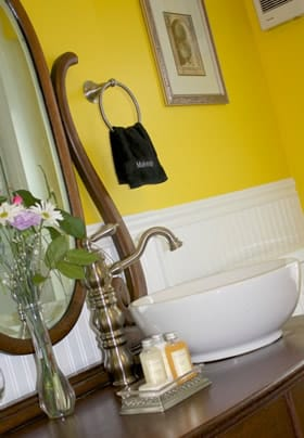 Prince Alfred guest bath with yellow walls, antique vanity with mirror and vessel sink, arched faucet, fresh flowers, and toiletries