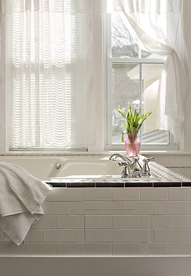 Princess Alice guest bath with white tiled tub and fresh flowers under double window with sun streaming through white sheers