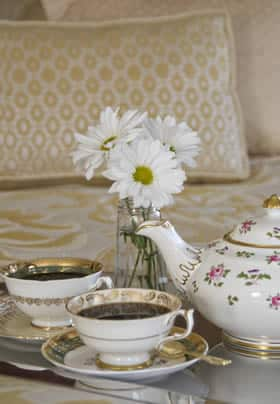 Silver tray topped with floral and ivory teacups, saucers, and teapot with small vase of white daisy flowers