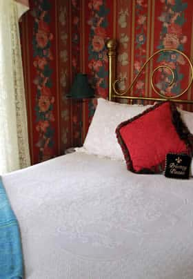 Princess Beatrice guest room with floral and striped papered walls, white bedding, and red pillow