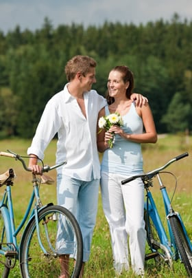 Man and woman standing arm in arm by their bicycles surrounded by a natural green landscape