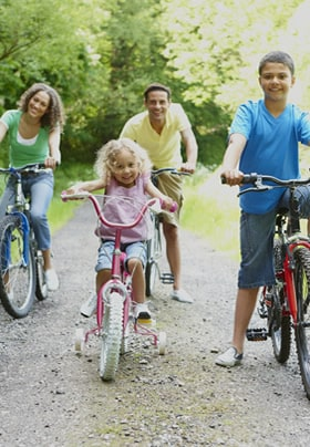 Mom, dad, and two children riding bicycles along a path surrounded by trees