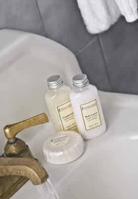 Close up view of Prince Leopold guest bath sink with antique brass faucet and toiletry samples