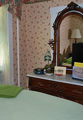Princess Louise guest room, floral papered walls, dresser with mirror and light green bedding
