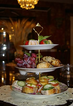Three tiered tray on an ivory doily topped with various fruit and desserts