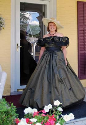 Penny dressed up in a fancy shimmery black off-the-shoulder dress with a white hat while standing on the front porch