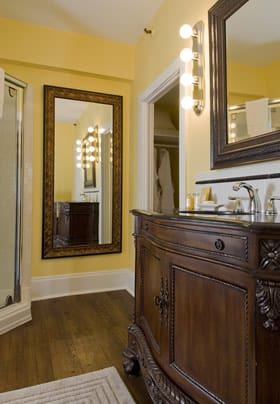 Princess Victoria guest bath with antique sink vanity, two mirrors, wood floor, yellow walls and corner shower