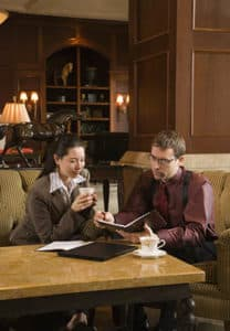 A couple, male and female, sitting at a coffee table browsing a portfolio.