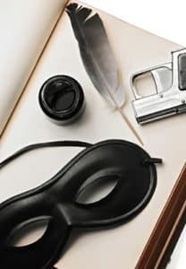 Murder Mystery suspense kit. Quill and ink, eye mask of midnight black, and fake derringer arranged in a box.