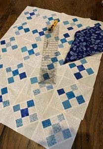 Alternating squares of blue being measured to form quilt squares.