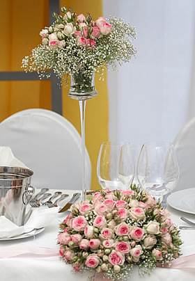 Wedding bouquet and vase on the bride and groom's table filled with variegated ivory and pink roses with baby's breath