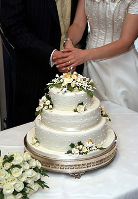 Bride and groom cutting into an ivory three-tiered wedding cake dressed with ivory roses and greenery