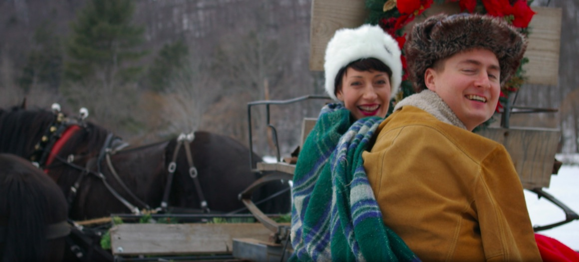 Couple bundled up in a sleigh.