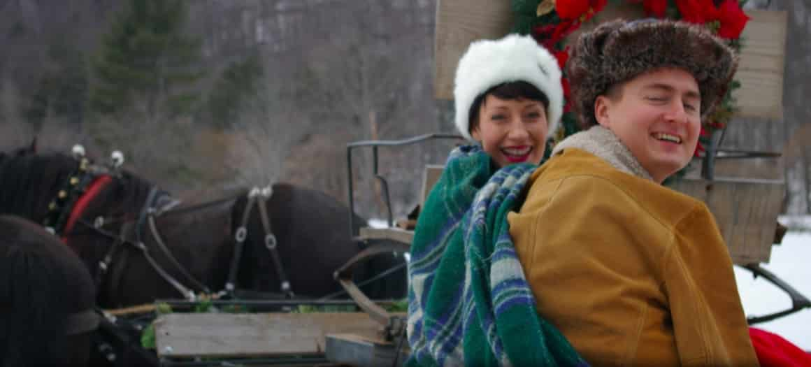 A photo of a couple bundled up on a sleigh ride.
